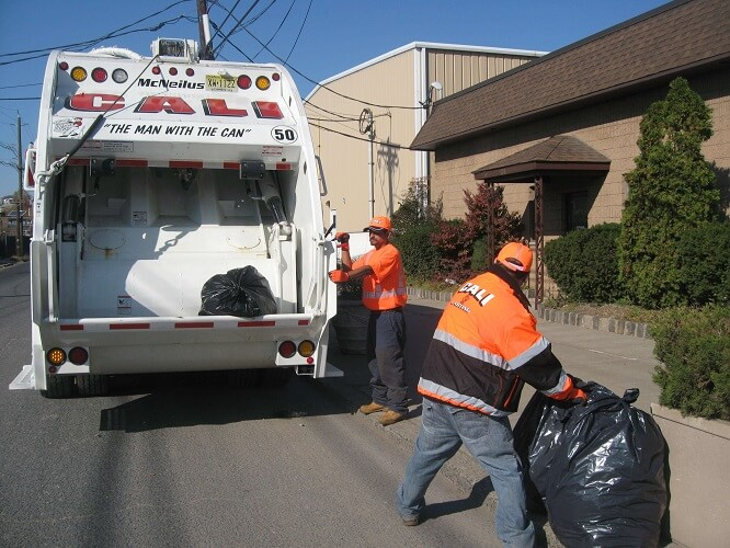 two male workers picking up trash and putting into the cali carting dumpster