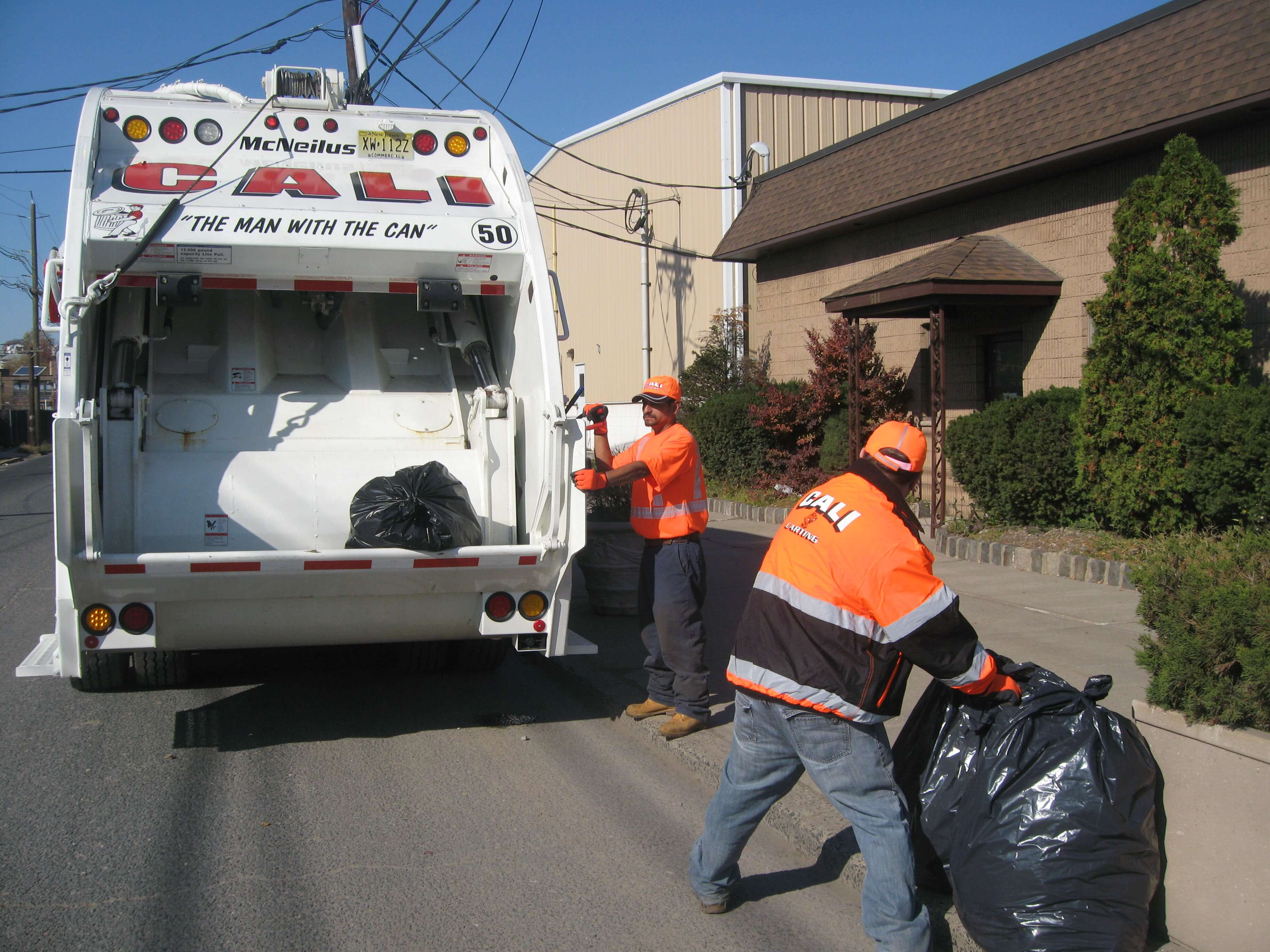 men picking up garbage with white cali carting truck